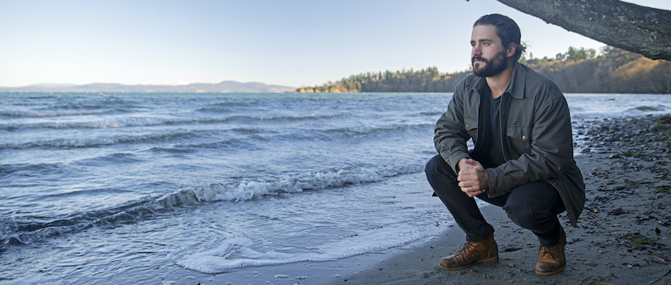 Brett Jameson kneels on a beach at the edge of the ocean.