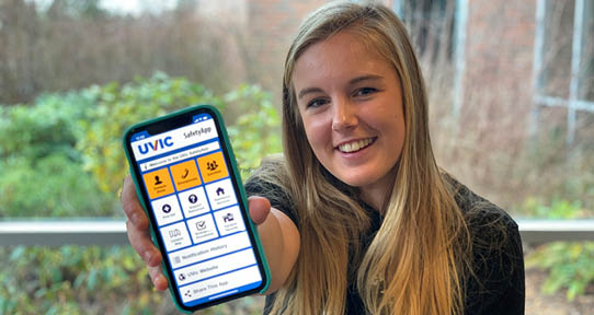 UVic student holds out a smart phone with the UVic Safety App showing on it
