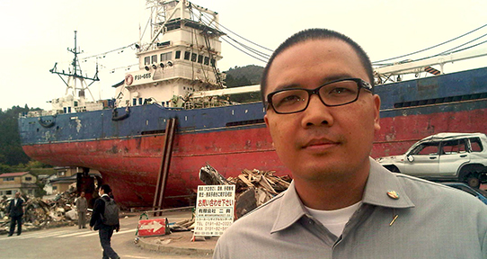 Santo Darmosumarto in front of a freight ship in Indonesia